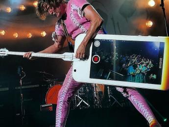 Stig Pedersen y su bajo con forma de iPhone que hace fotos al publico