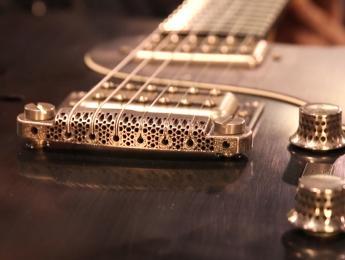 Un puente de guitarra impreso en 3D con metal amorfo diseñado por el luthier Nik Huber